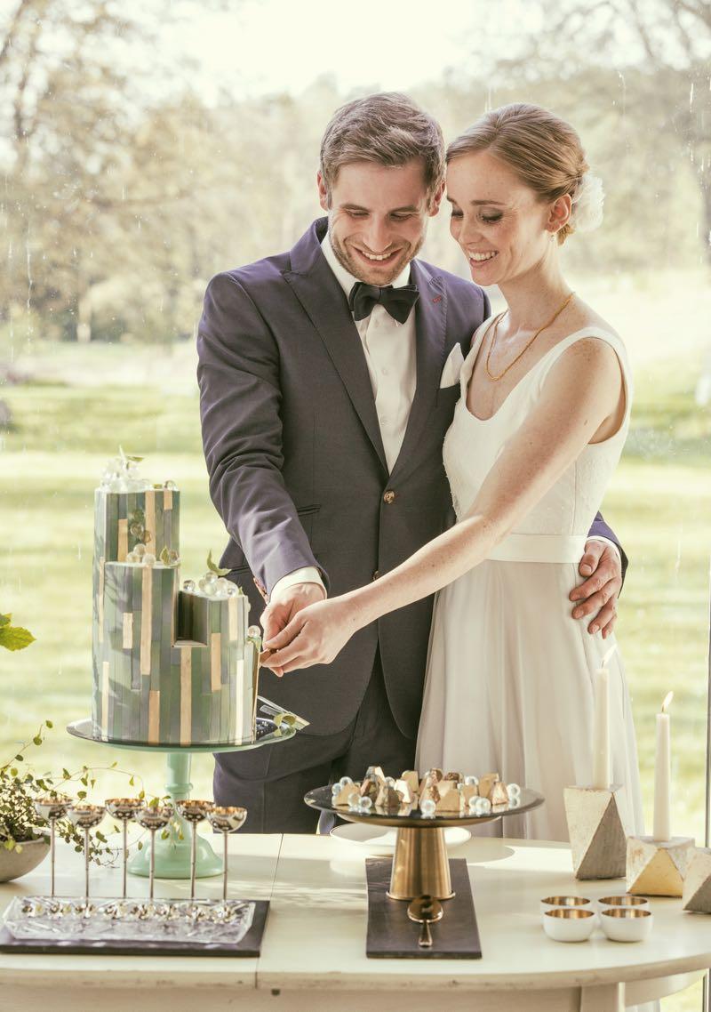 Brautpaar beim Anschneiden ihrer Design-Hochzeitstorte.