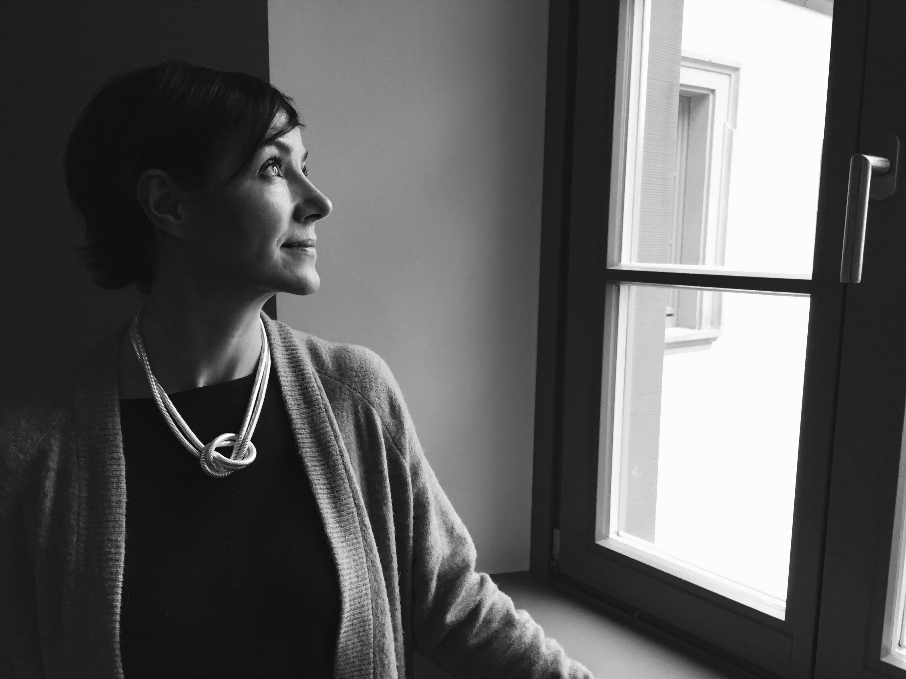 Frau am Fenster, über Vorsätze nachdenkend.