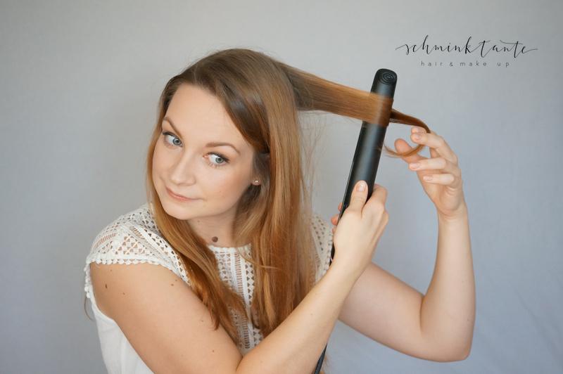 Model mit Glätteisen beim Haarstyling.